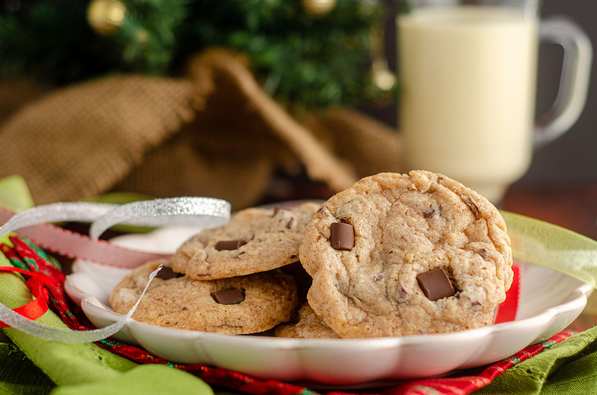 eggnog chocolate chunk cookies sitting on a plate with christmas ribbons around it