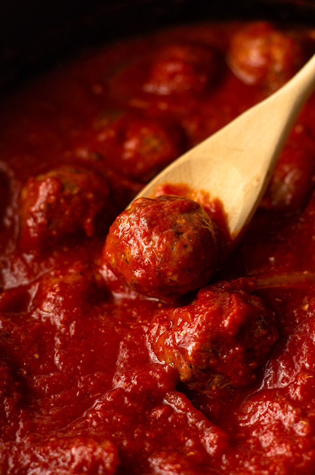 gluten free meatballs in a slow cooker with a wooden spoon