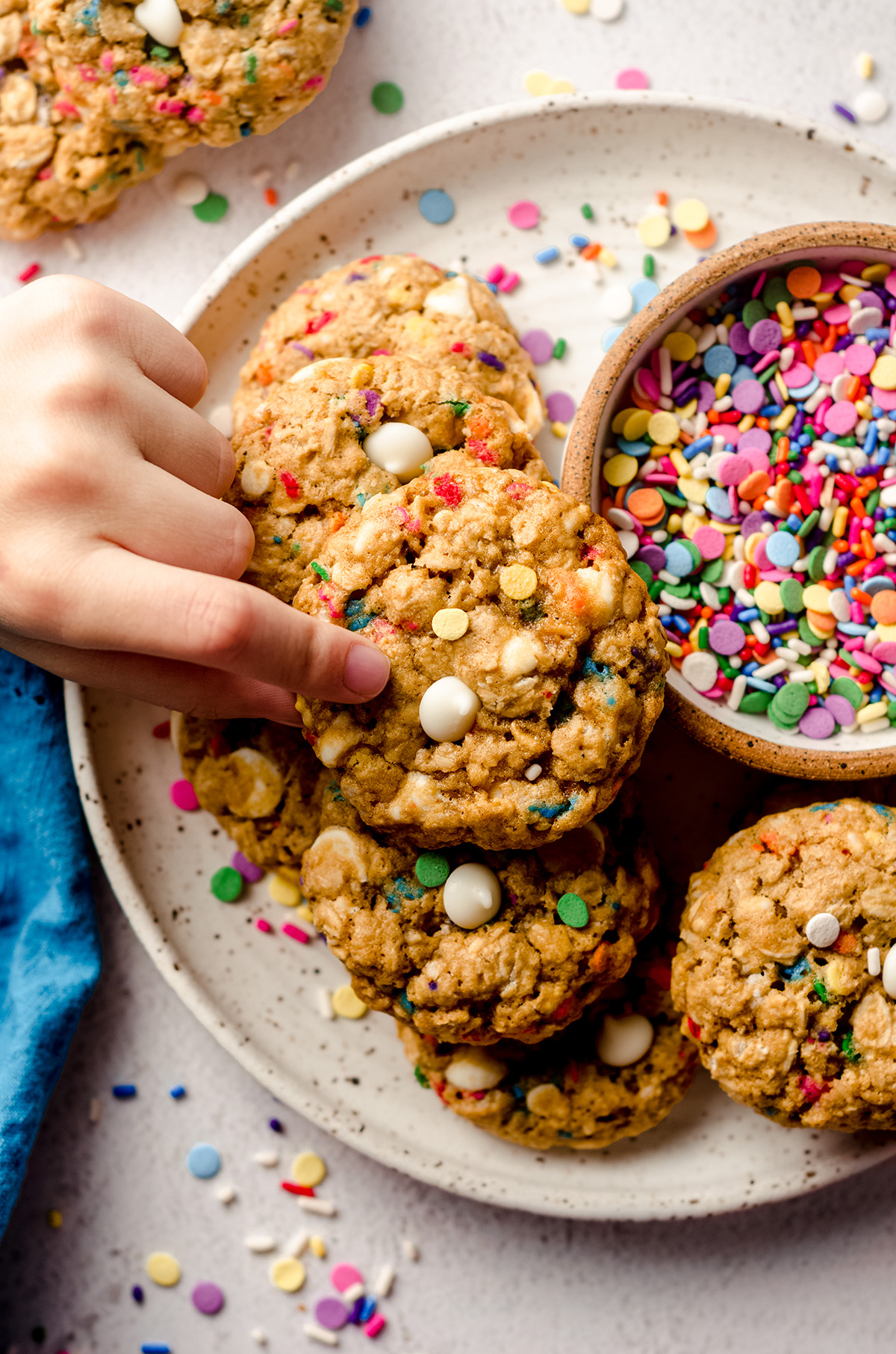 aerial photo of a child's fingers picking up a funfetti oatmeal cookie up from a plate of cookies