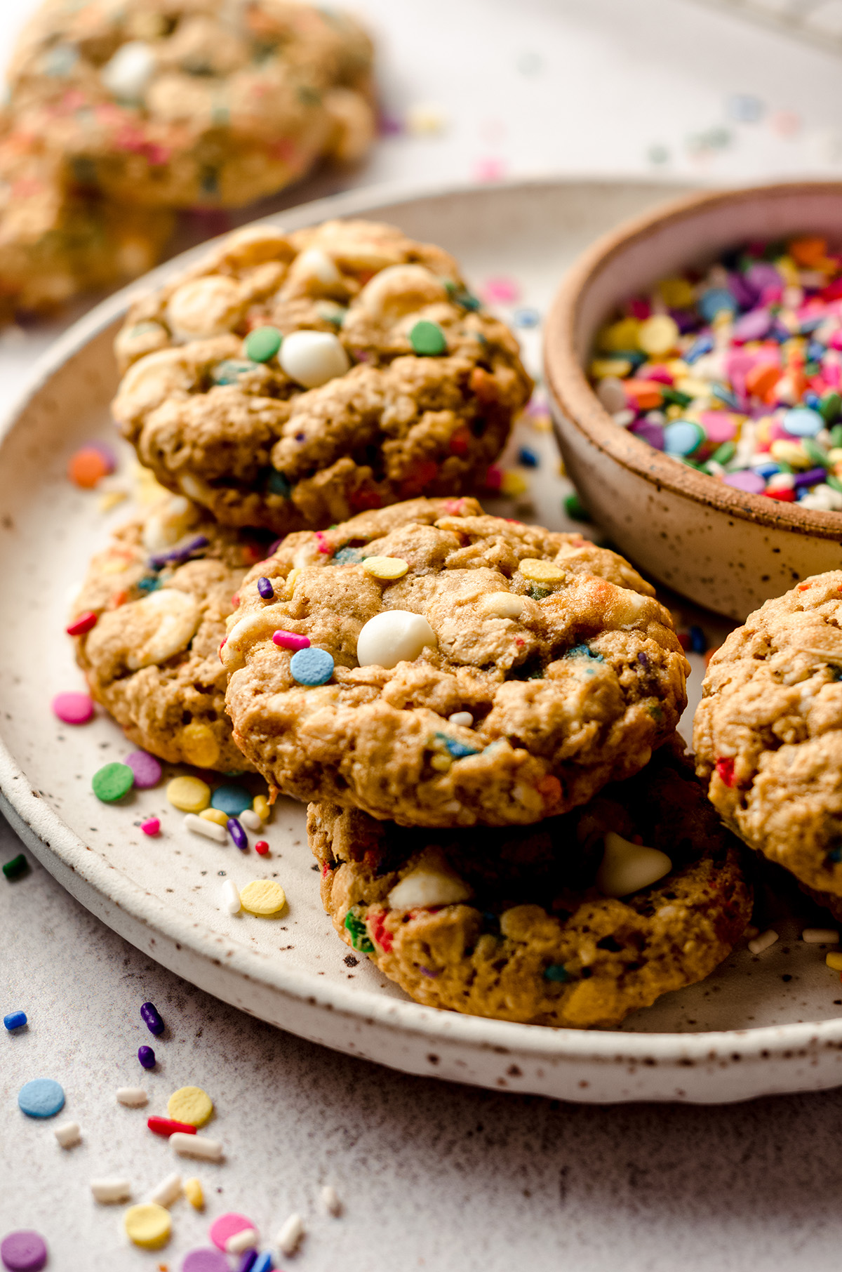 funfetti oatmeal cookies on a plate with a bowl of sprinkles