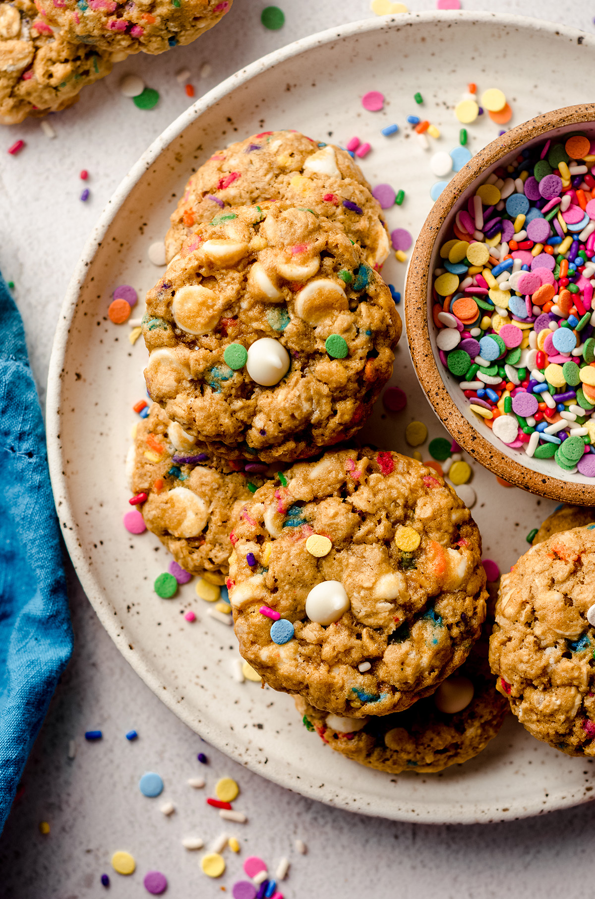 aerial photo of funfetti oatmeal cookies on a plate with a bowl of sprinkles