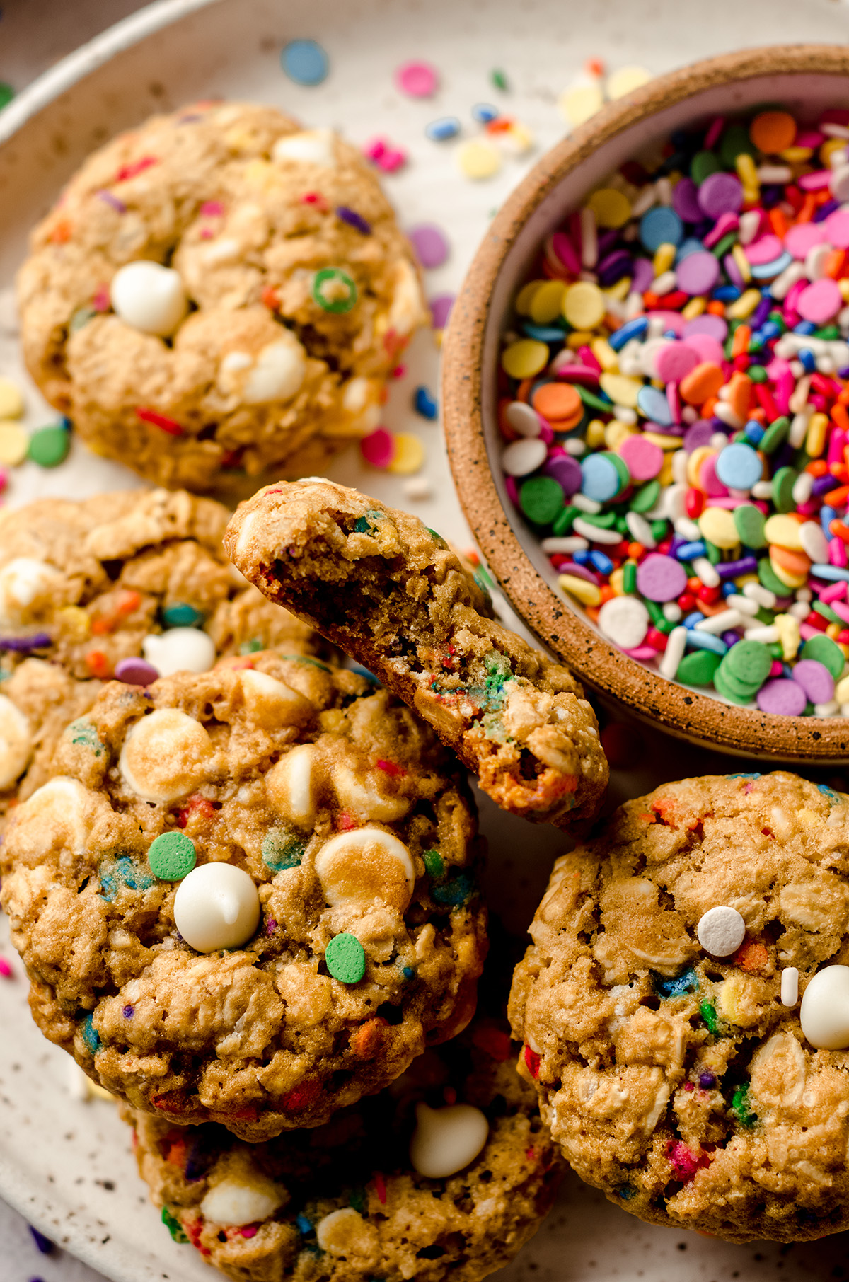 funfetti oatmeal cookies on a plate with a bowl of sprinkles and one cookie has a bite taken out of it