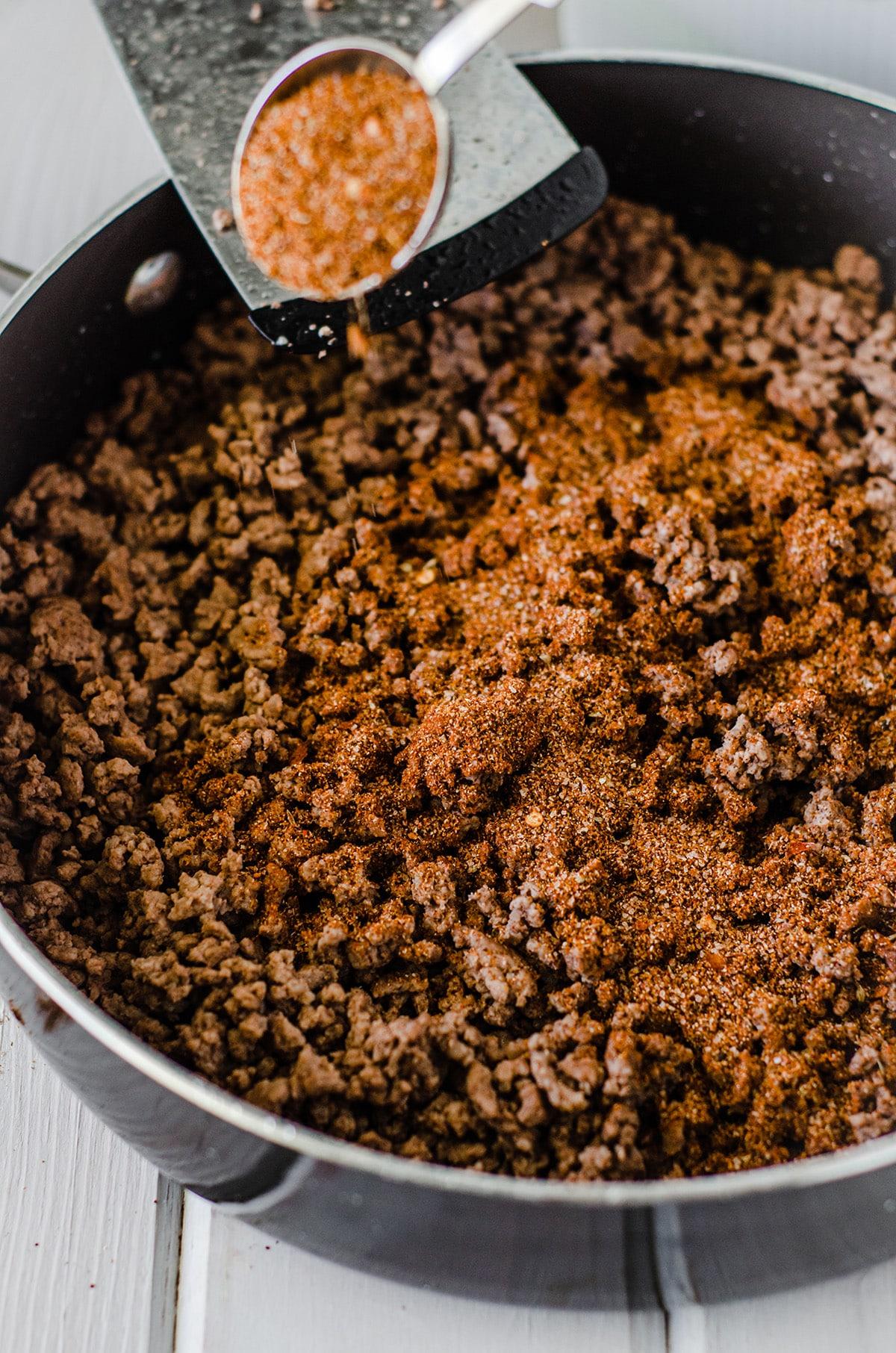 sprinkling homemade taco seasoning on browned meat
