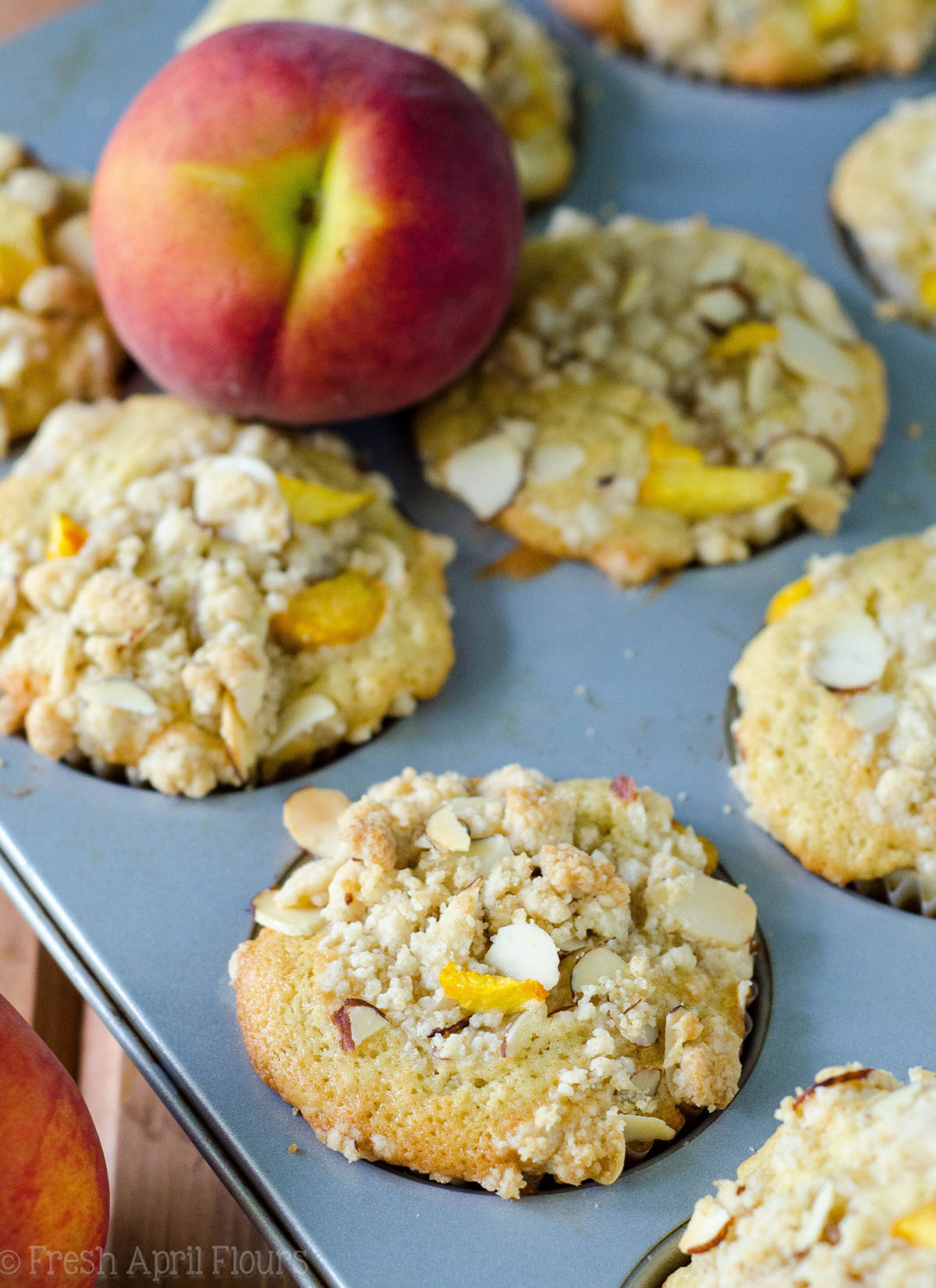 Moist and tender peach muffins, accented with almond extract and topped with a sweet and crunchy almond streusel.