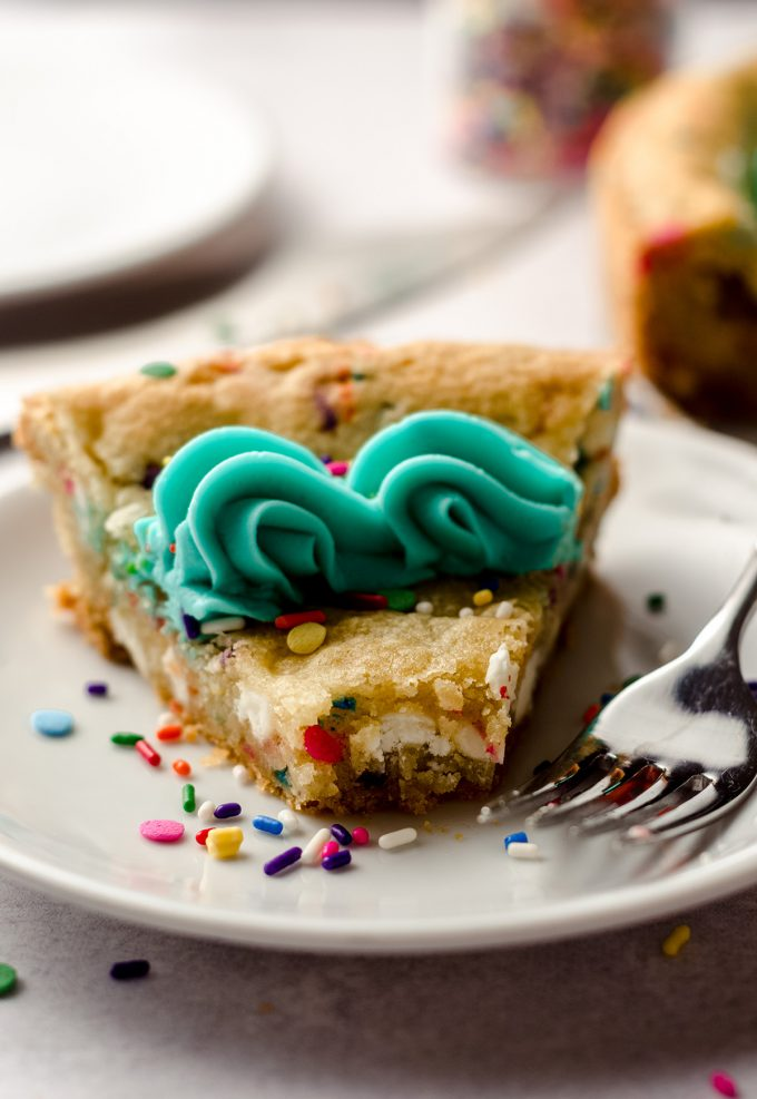 a slice of funfetti sugar cookie cake on a plate with a bite taken out of it