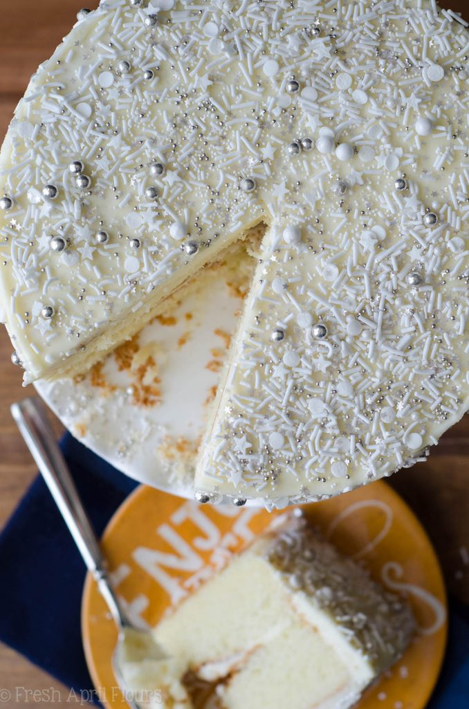 aerial photo of white layer cake with white and silver sprinkles all over it and a slice of cake removed and on a yellow plate in the background