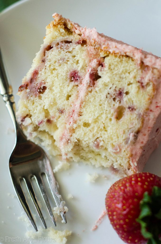 fresh strawberry cake on a plate with a fork and a bite taken out of it