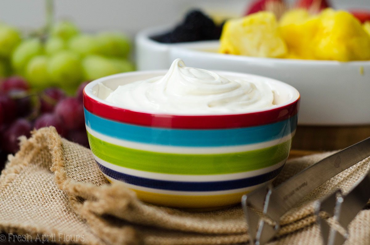 fruit dip in a bowl with a platter of fruit behind it