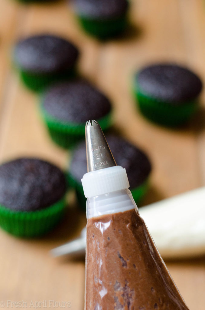 chocolate frosting in a piping bag to make football cupcakes