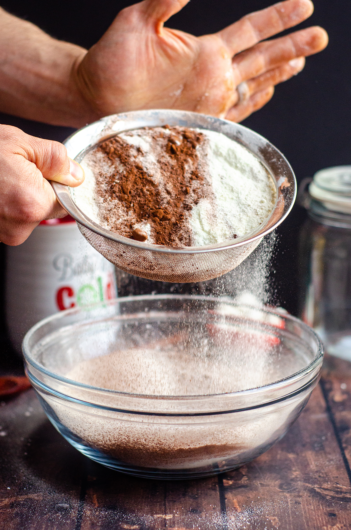 sifting powdered sugar and cocoa powder into a bowl for homemade hot cocoa mix