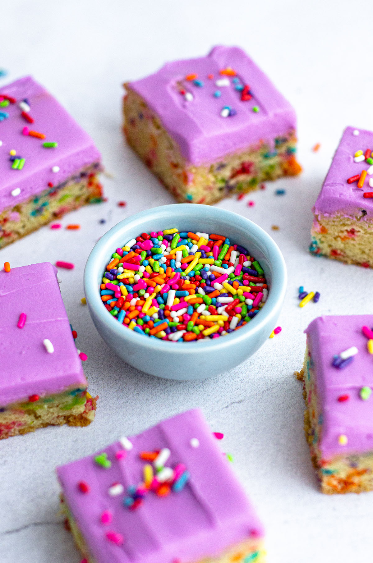 small bowl of rainbow sprinkles surrounded by sugar cookie bars
