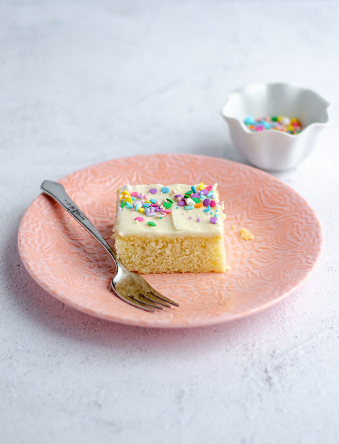 slice of white sheet cake on a pink plate