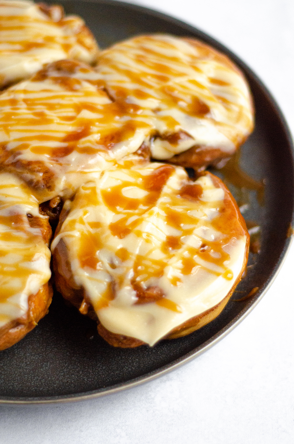 caramel rolls with caramel cream cheese frosting on a plate