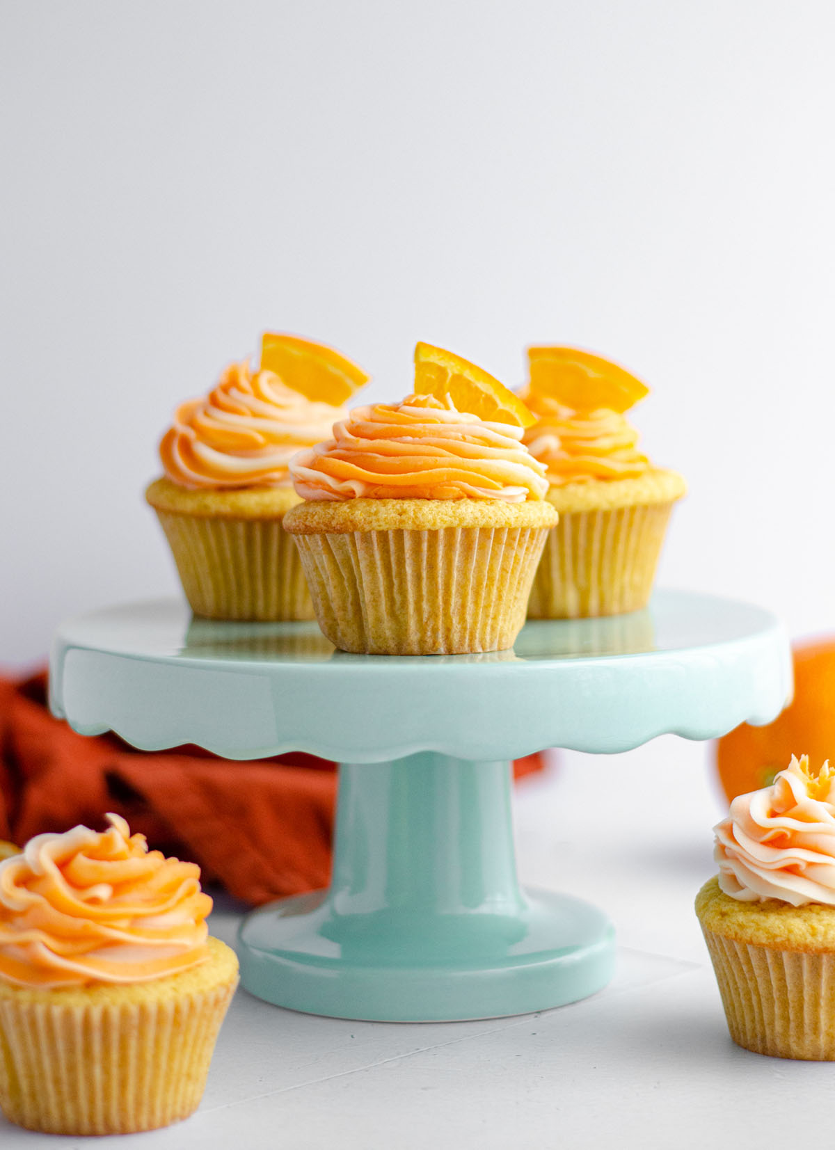 orange creamsicle cupcakes on a light blue cupcake stand