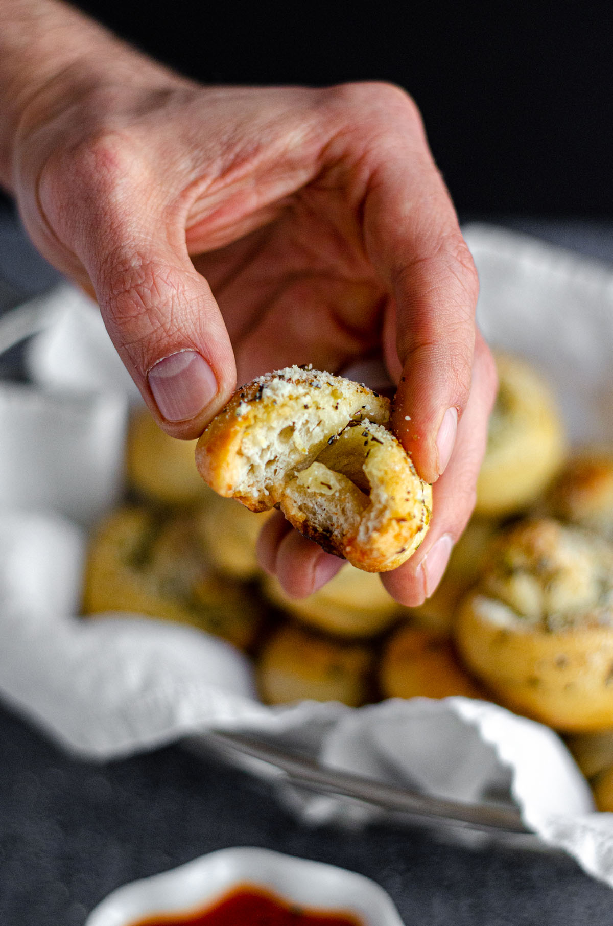 hand holding a homemade garlic knot with a bite taken out of it