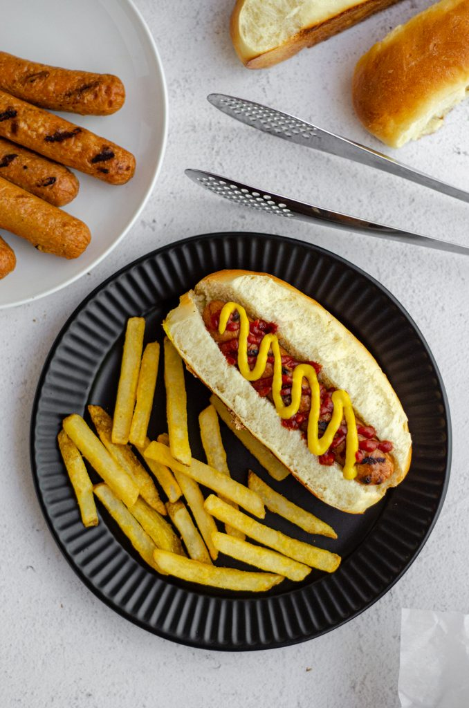 aerial photo of hot dog in a homemade hot dog bun with a squirts of ketchup and mustard sitting on a black plate with french fries