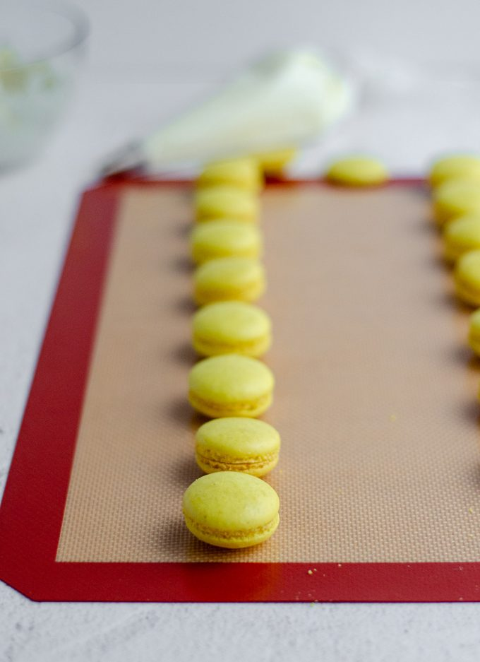 lemon macarons on a baking sheet getting ready to assemble with frosting on the inside