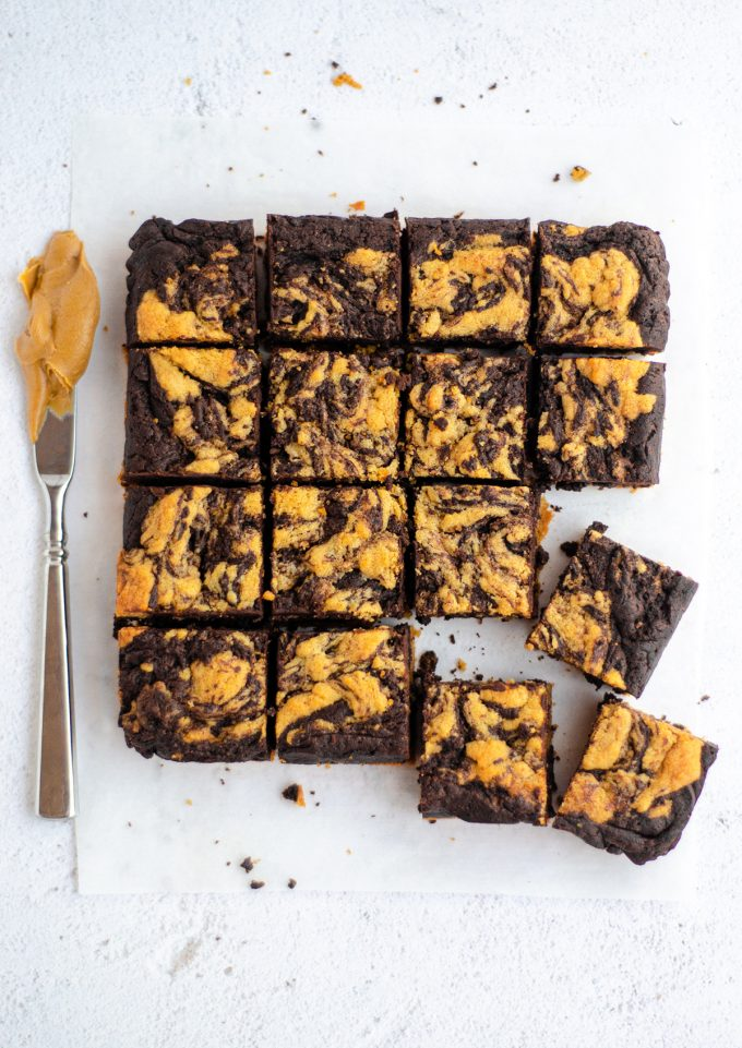 aerial photo of sliced peanut butter cookie brownies with a knife covered in peanut butter next to them