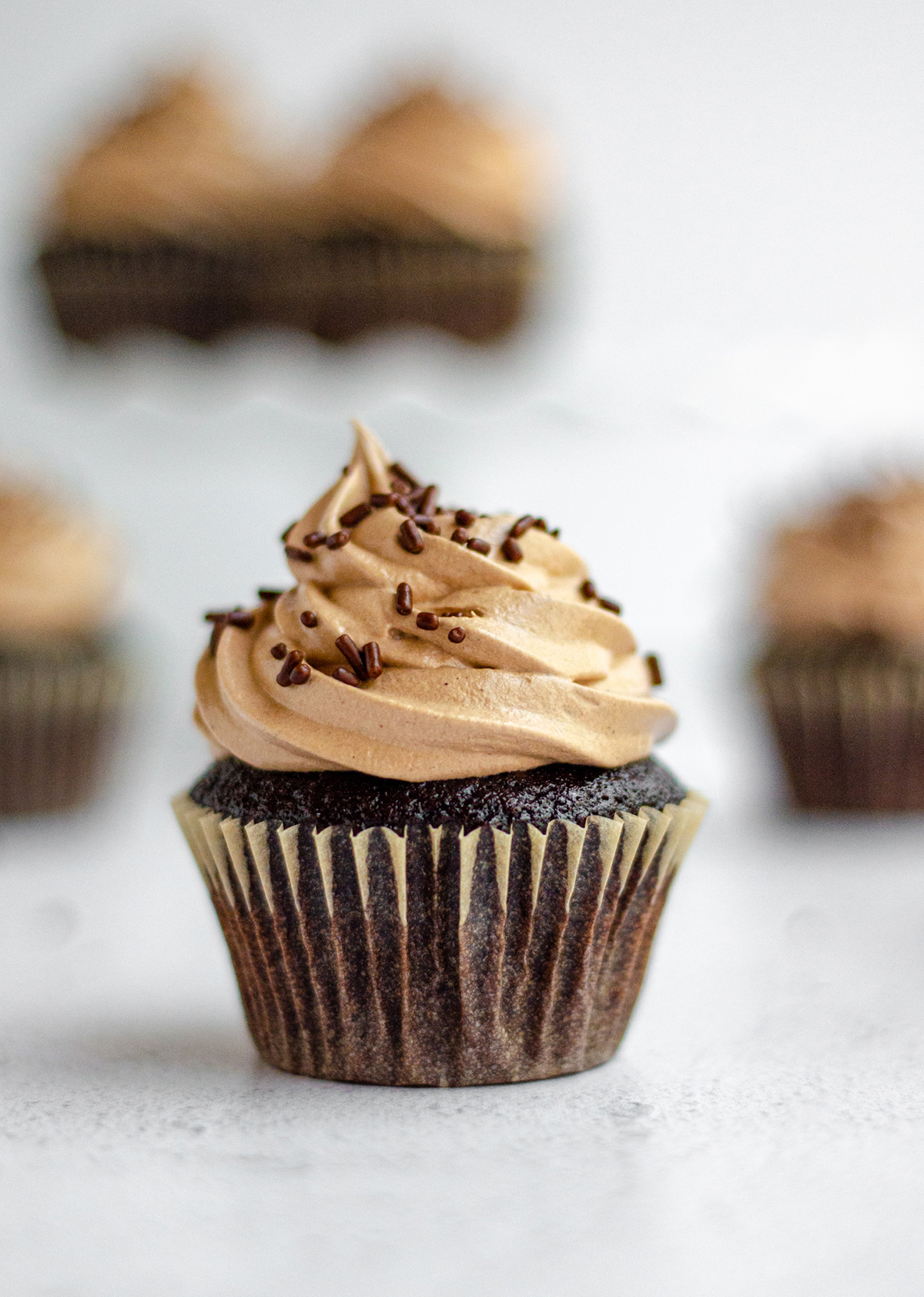simple chocolate cupcakes with chocolate swiss meringue buttercream and chocolate sprinkles on top