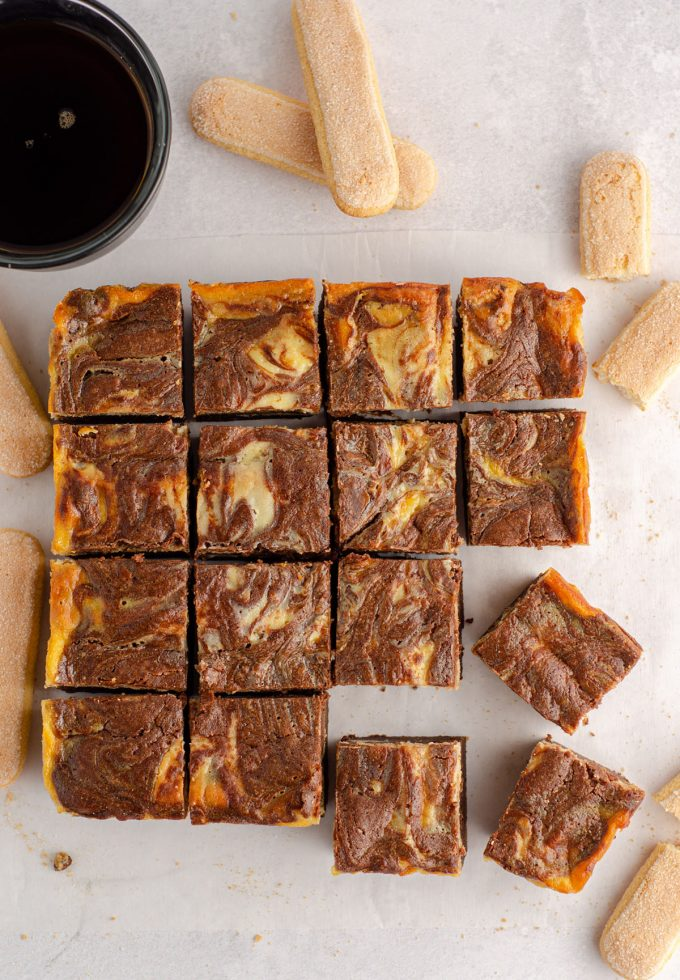 aerial photo of sliced tiramisu brownies on parchment paper with a cup of coffee and ladyfingers