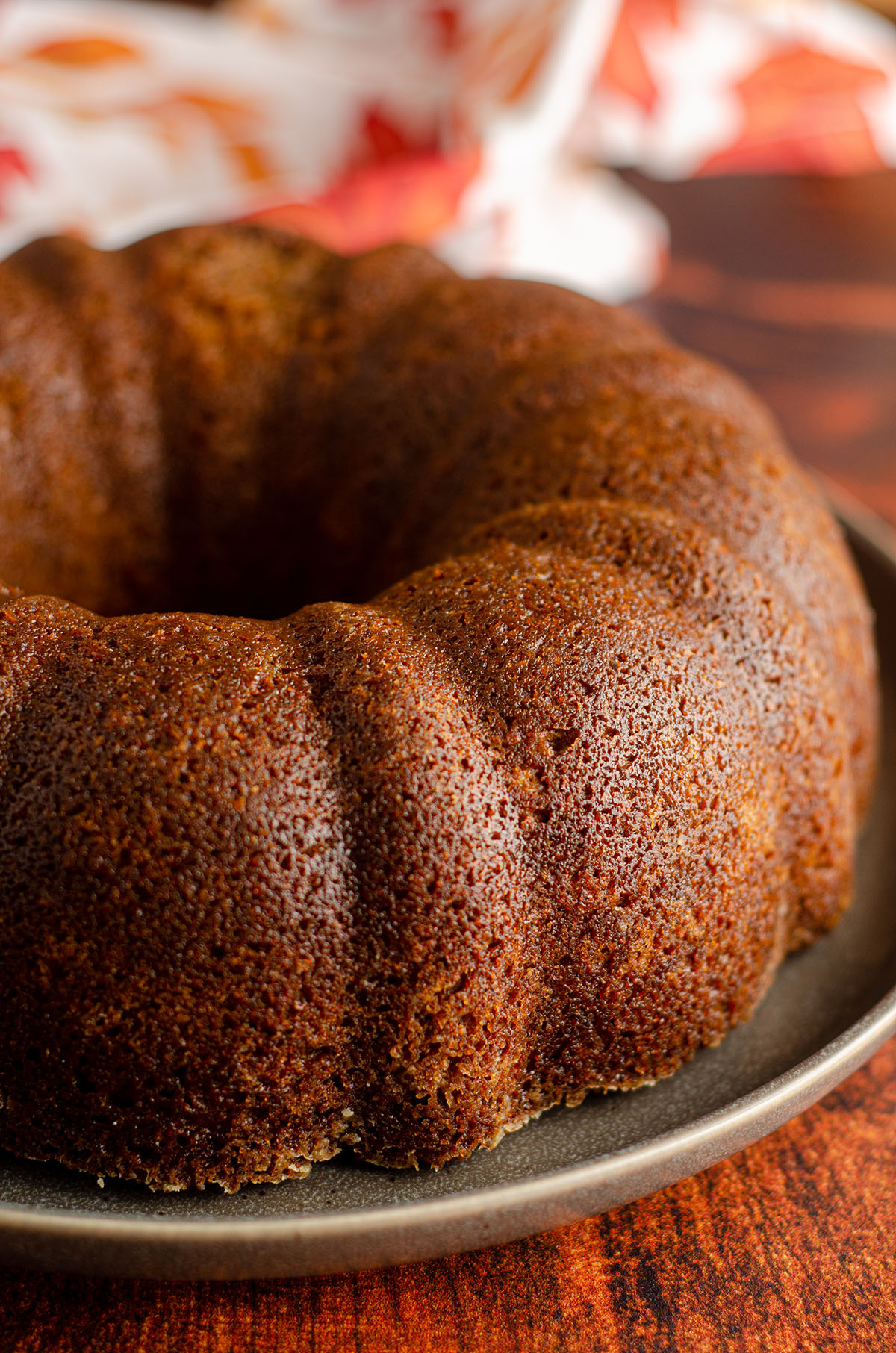 Pumpkin pumpkin bundt cake sitting on a plate without frosting Cake: Moist, spiced bundt cake made with real pumpkin and covered in a decadent brown butter buttercream.