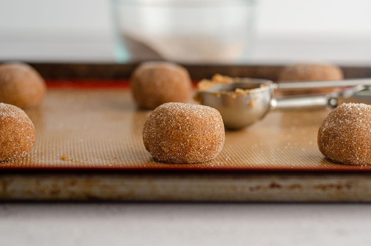balls of pumpkin spice cookie dough on a baking sheet