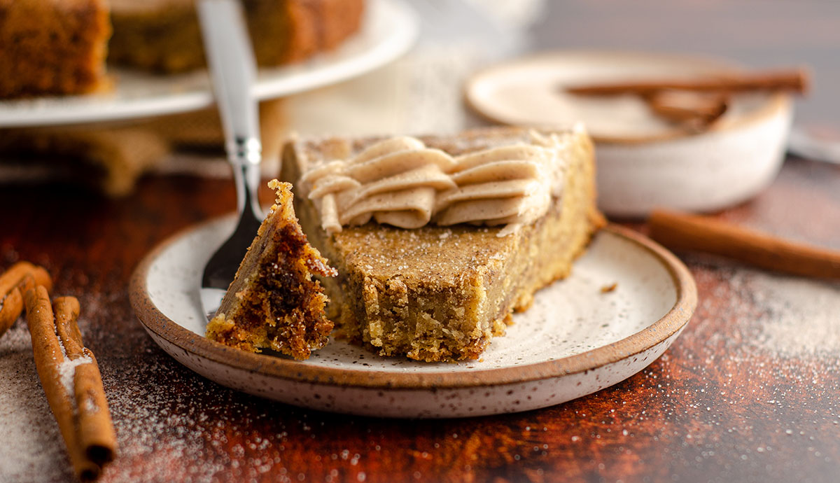 snickerdoodle cookie cake sitting on a ceramic plate with a bite taken out and sitting on a fork