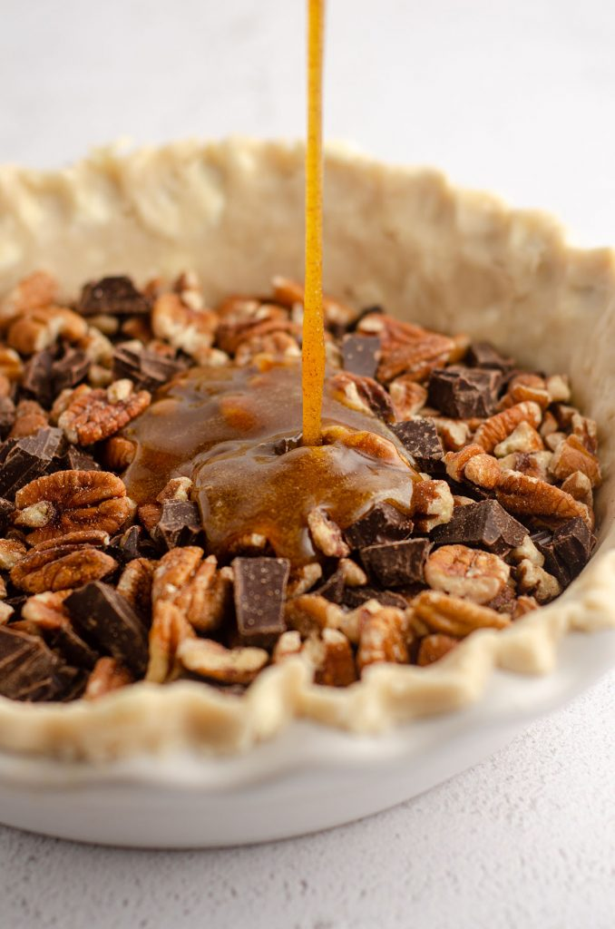 filling being poured into pie plate with a pie crust fitted into it, pie plate is filled with pecans and chocolate chunks
