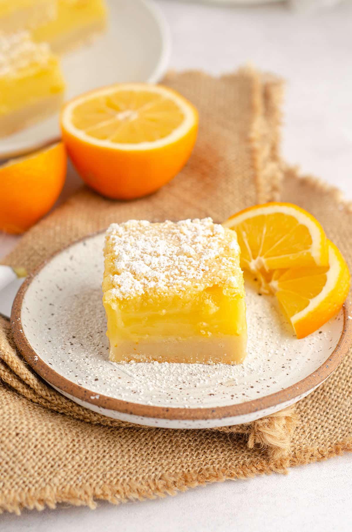 meyer lemon bar sitting on a plate with slices of meyer lemon
