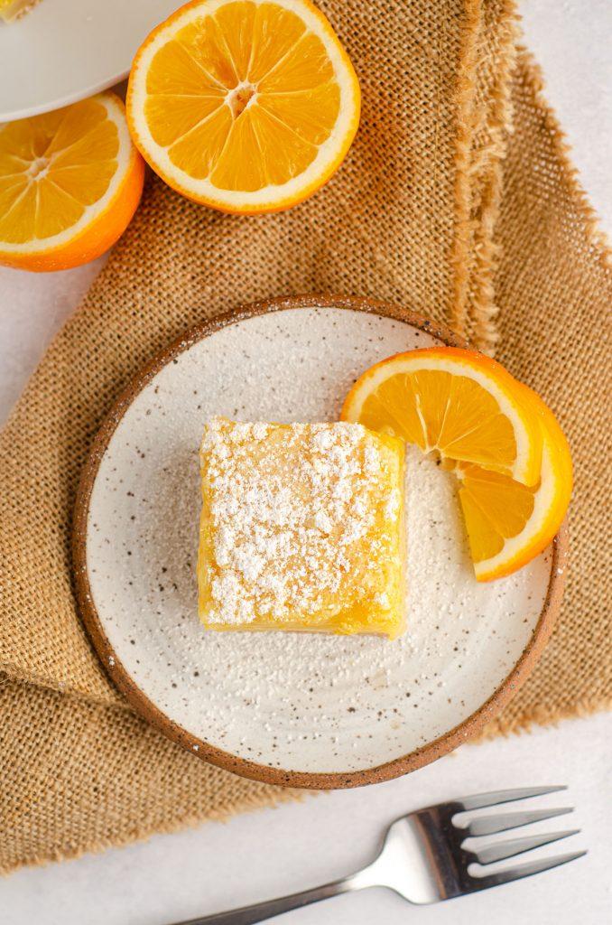 aerial photo of meyer lemon bar sitting on a plate with slices of meyer lemon