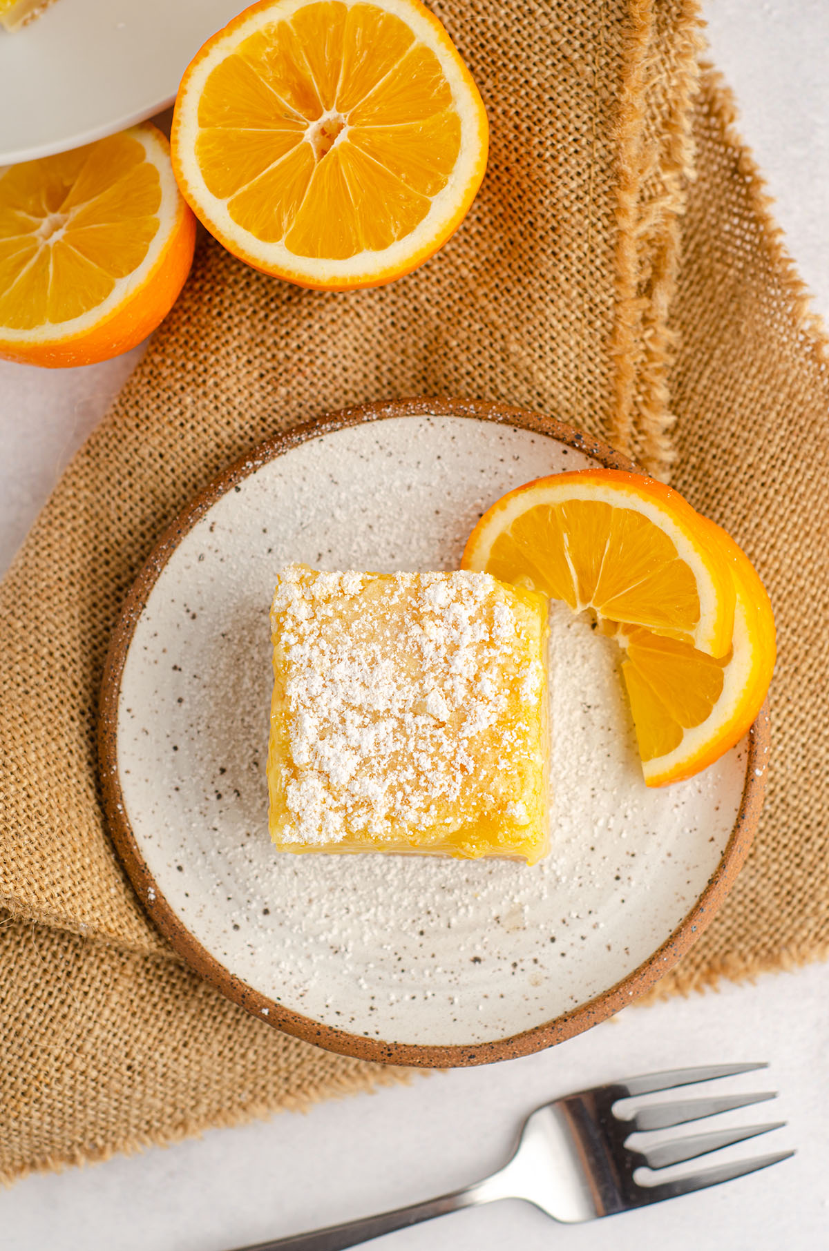 aerial photo of meyer lemon bar sitting on a plate with slices of meyer lemon