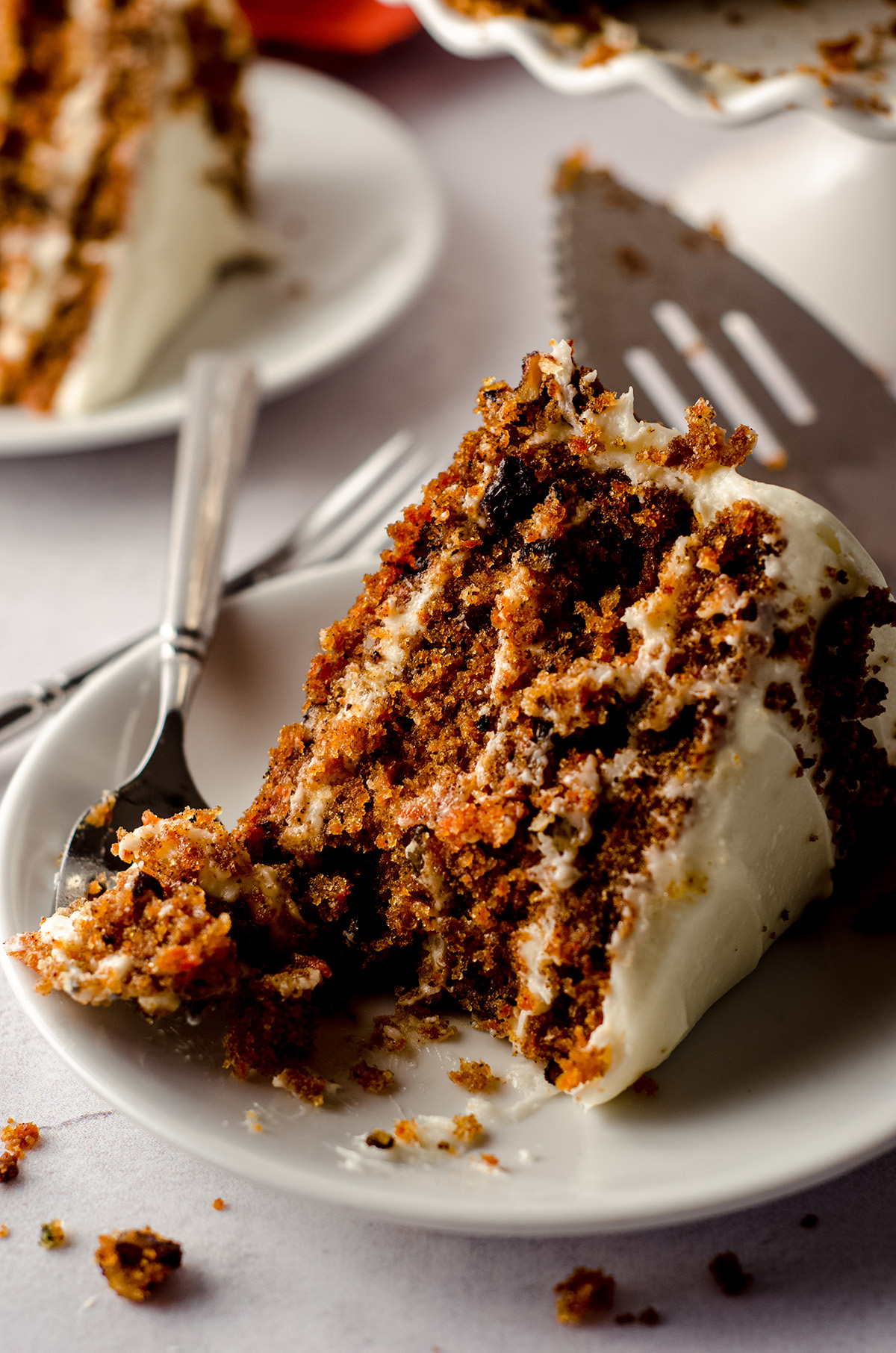 slice of carrot walnut cake on a white plate with a fork