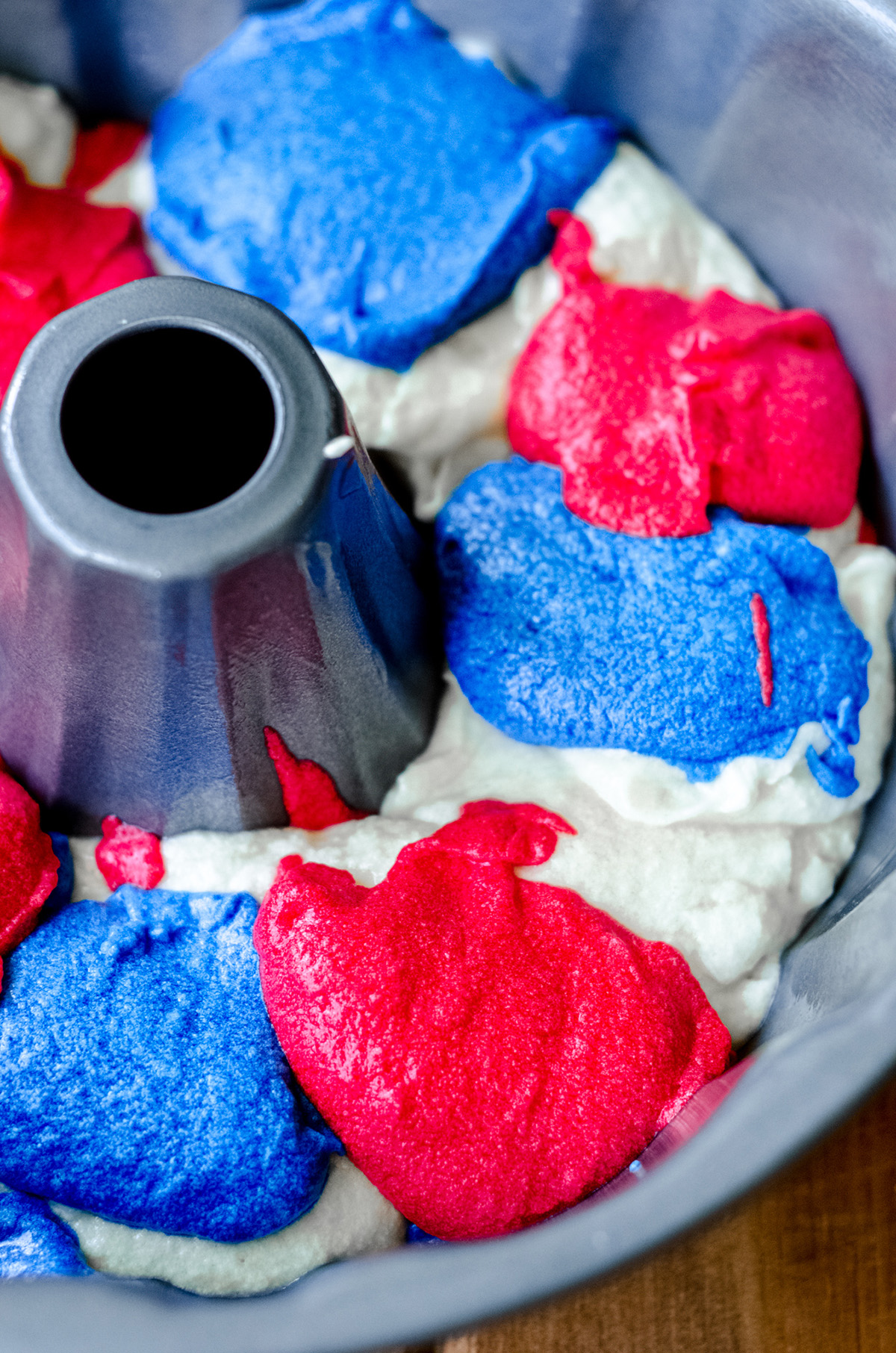 red white and blue swirl cake batter in a bundt pan