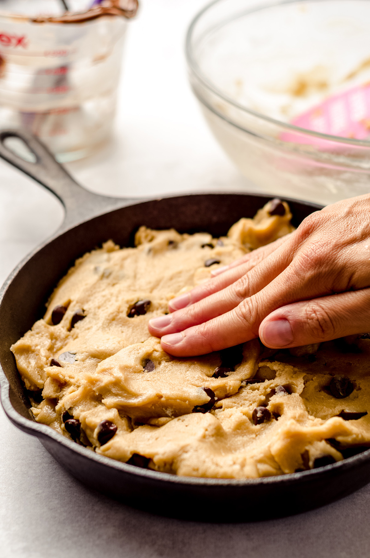 pressing cookie dough together in a skillet cookie
