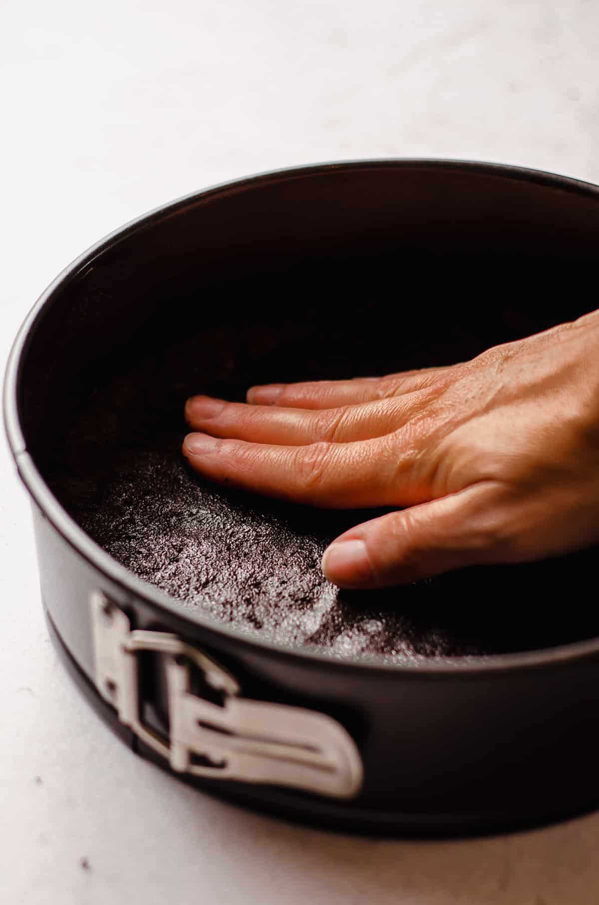pressing oreo crust into a springform pan