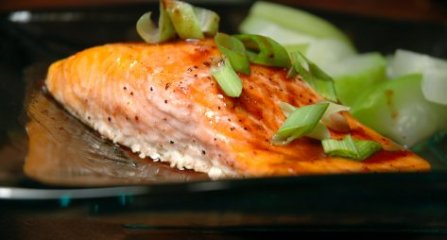 Glass plate with a steelhead salmon fillet and steamed summer squash