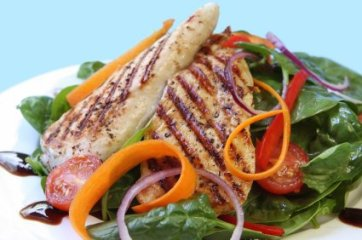 Grilled chicken breast on a spinach salad. Delicious healthy eating.