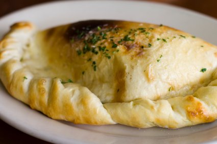 Baked Calzone on a white plate with shallow depth of field
