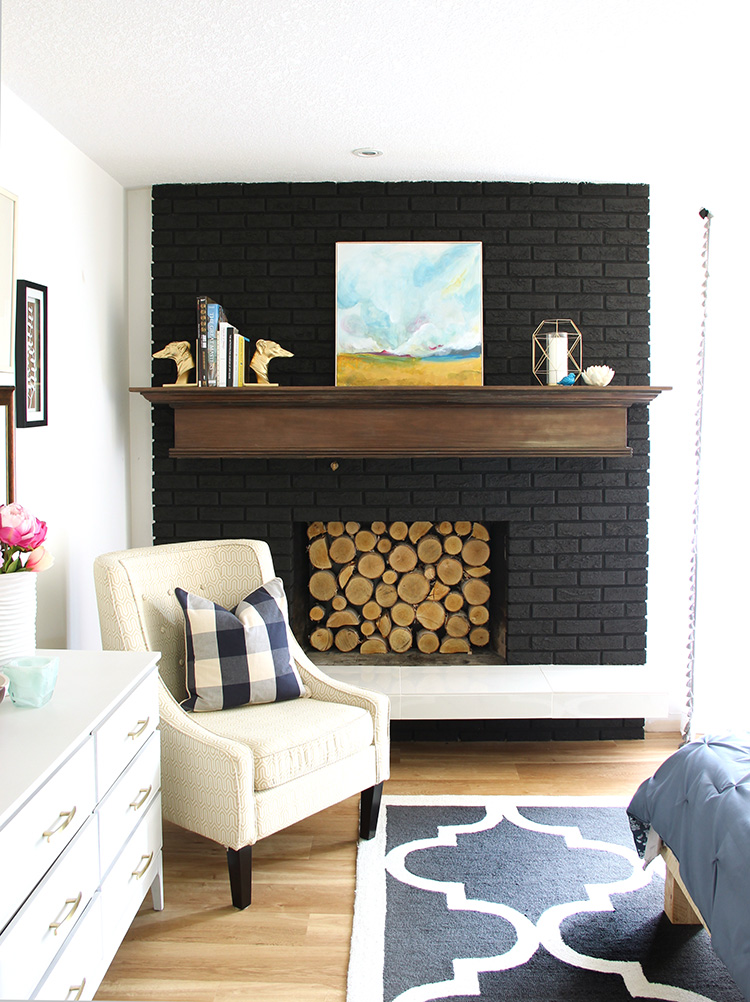 Black brick fireplace makeover with birch wood slice insert in bedroom makeover. Full home renovation with floor plans during one bloggers home improvement journey.