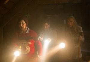 Allison Tolman, Adam Scott and Toni Collette find something horrific in the attic in KRAMPUS. Courtesy of Universal Pictures.