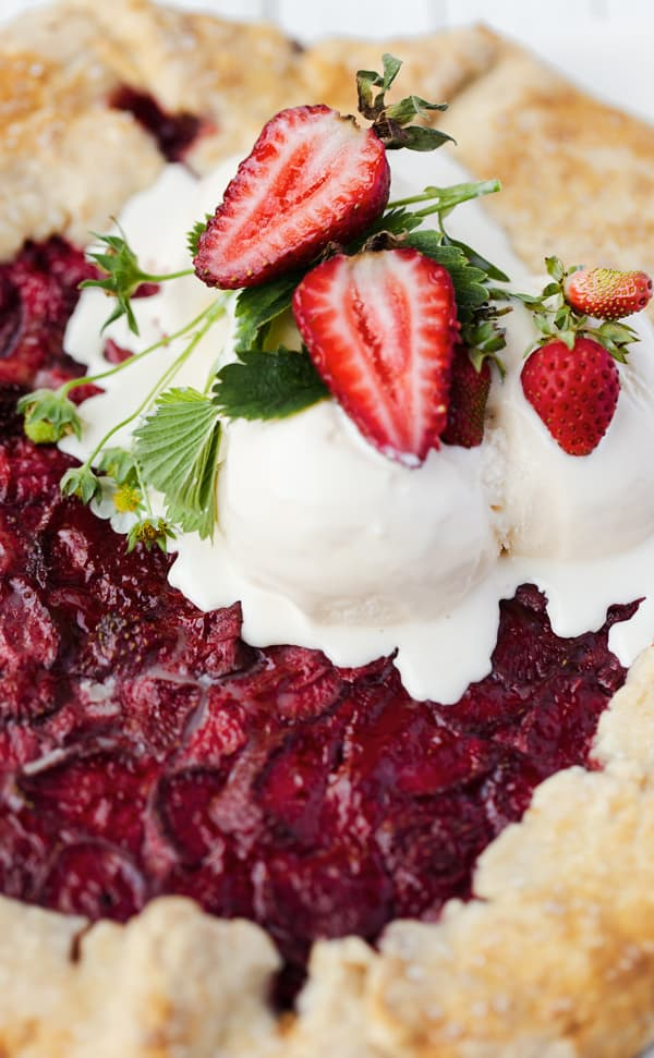 An easy -to-make impressive dessert with crisp pastry and jammy fruit filling Lemon Curd Wild Strawberry Galette is perfectly suited for summertime travel! Strawberry galette   wild strawberry galette crostata recipe   rustic pie   galette dough pie crust recipe   strawberry recipes   lemon curd   strawberry lemon