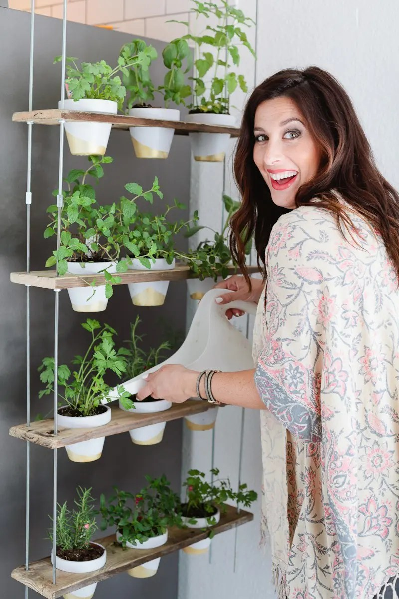 Make this Custom Potted Hanging Herb Garden. An easy DIY for your home made from pallet wood and inexpensive terra cotta pots! - Click through for the full tutorial. - Hanging Herb Garden DIY by popular Florida lifestyle blogger Fresh Mommy Blog