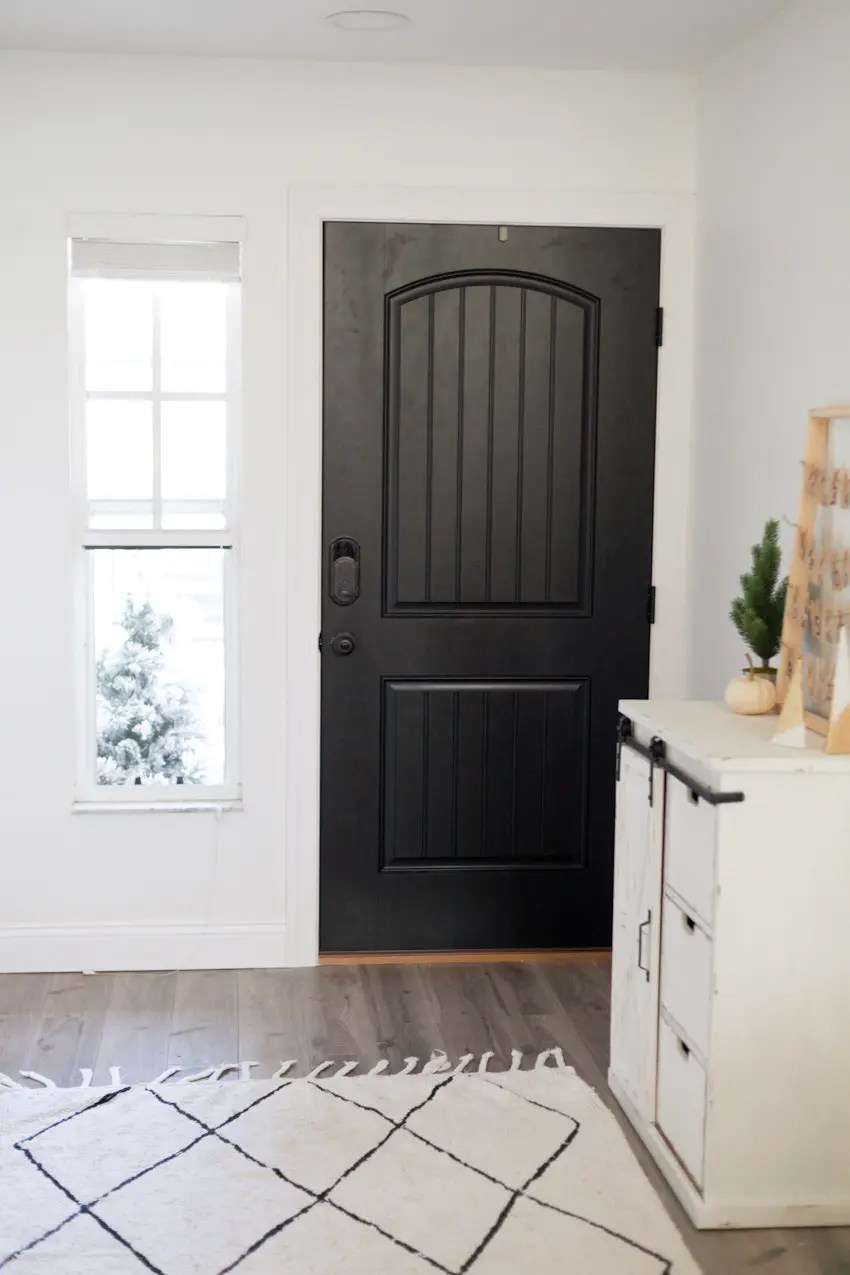 Modern farmhouse front entryway makeover reveal! Open your front door to guests this Christmas season with an updated front door. Black and white with wood natural elements make a welcoming statement and up the curb appeal.