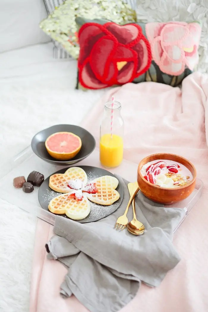 Valentine's Day Breakfast in Bed full of all things sweet, pink and delicious, of course! Heart waffles and strawberries and cream smoothie bowl, that tastes like ice cream, steal the show in this morning breakfast tray styled for your valentine. - Valentines Day Breakfast in Bed with Strawberry Smoothie Bowl by popular Florida lifestyle blogger Fresh Mommy Blog