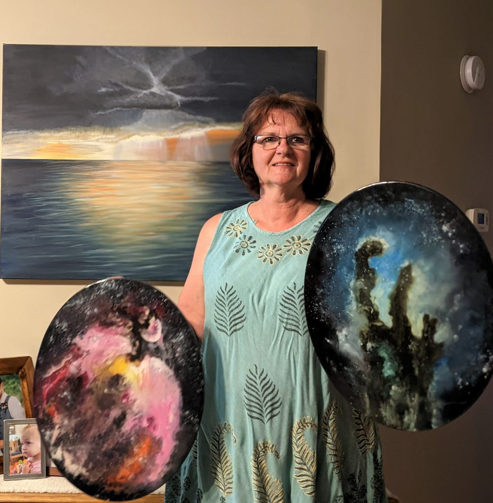 Laurie holding space paintings