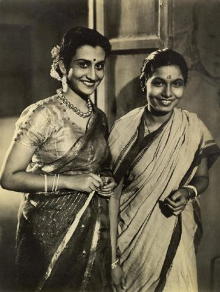 Indian movie actresses. Dressed in Sarees, 19-year old Binota Bose, left, and Mrs. Rekha Mullick, right,are right at home before the camera and lights. Miss Bose earns $360.00 per month and Mrs. Mullick $210.00. Both are well educated and prefer American books, pictures.