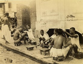 Sidewalk tonsorial parlor. India probably has a greater proportion of barbers than any nation, for in addition to the many salons which cater to the European and higher type Indian trade, these sidewalk shavers seem to ply their trade in every other block.