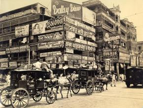 A bewildering mass of billboards at the corner of Harrison Street (Burra Bazar) and Strand Road. One of the oldest secions of Calcutta, at the foot of Howrah Bridge, it is a fine vantage point for photo-graphing the passing parade of oddly dressed natives and curious vehicles.