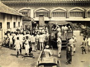 Crowd gathers round a sidewalk performer at bus stop while GI's take temporary advantage of an overheadview from steps of a camp bus. This is a good spost for hawkers, beggars, shoe shine boys, showmen to work on the bankroll of the 'rich American soldier'.