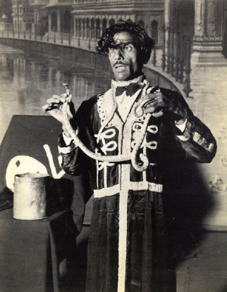 Believe it or not, this man has just bitten the head from a live Krait snake. He is professor Sher Mohammed and his feats include drinking acid, eating glass, fire-walkig. He is a legitimate performer and has spent the war years touring for the entertainment of Indian troops rather than poach on sidewalk tourists.